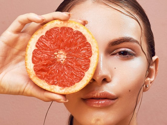 Sensual young woman with bright makeup holding delicious grapefruit in her hand